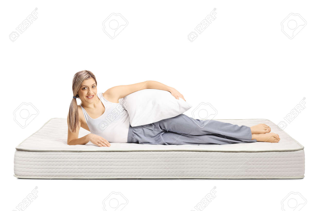 Young woman lying on a bed mattress in pajamas and holding a pillow isolated on white background - 158902314