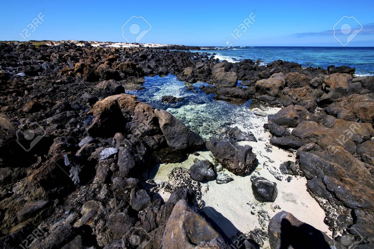 sky light beach water in lanzarote isle foam rock spain landscape