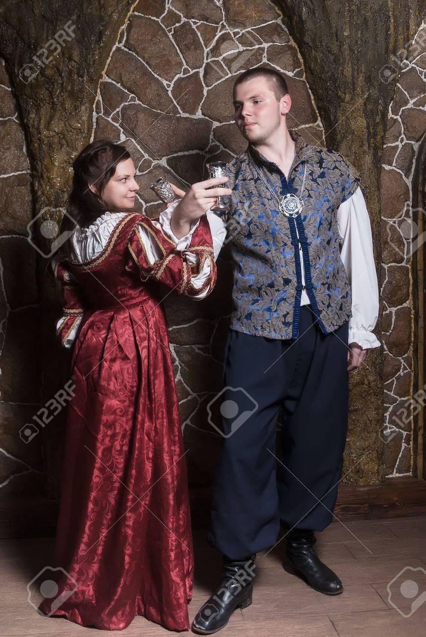schöne paare, die frau und mann in der mittelalterlichen kleidung im zimmer