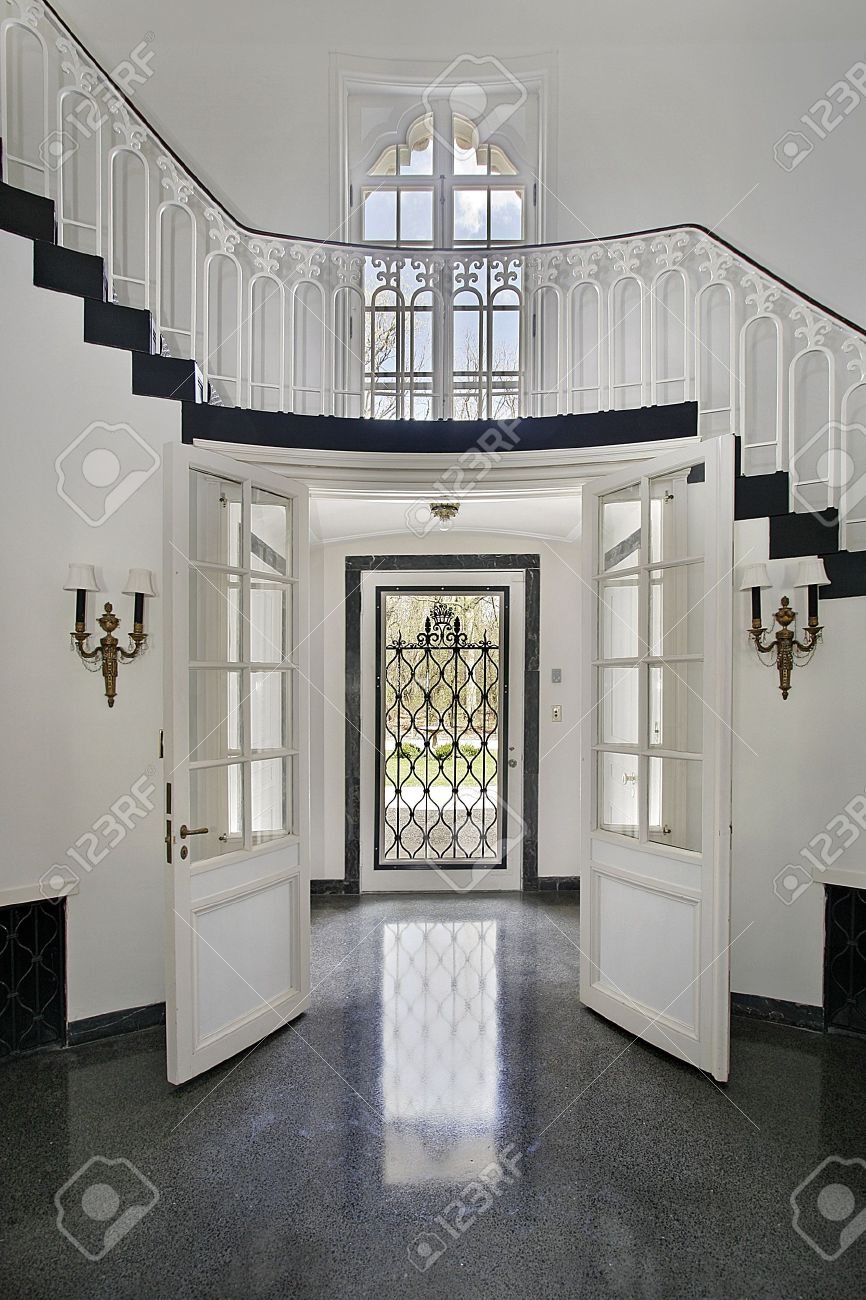 Traditional foyer with double entry door and staircase stock photo ...