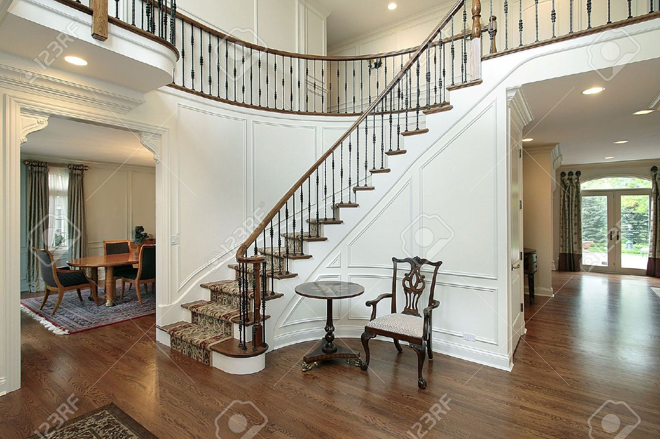 Foyer with curved staircase in luxury home stock photo, picture ...
