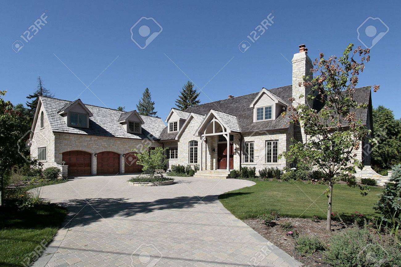 luxury stone suburban home with three car garage stock photo