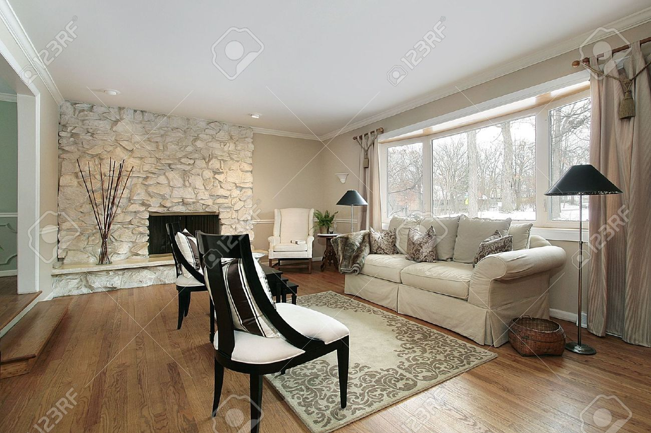 living room in luxury home with stone fireplace stock photo