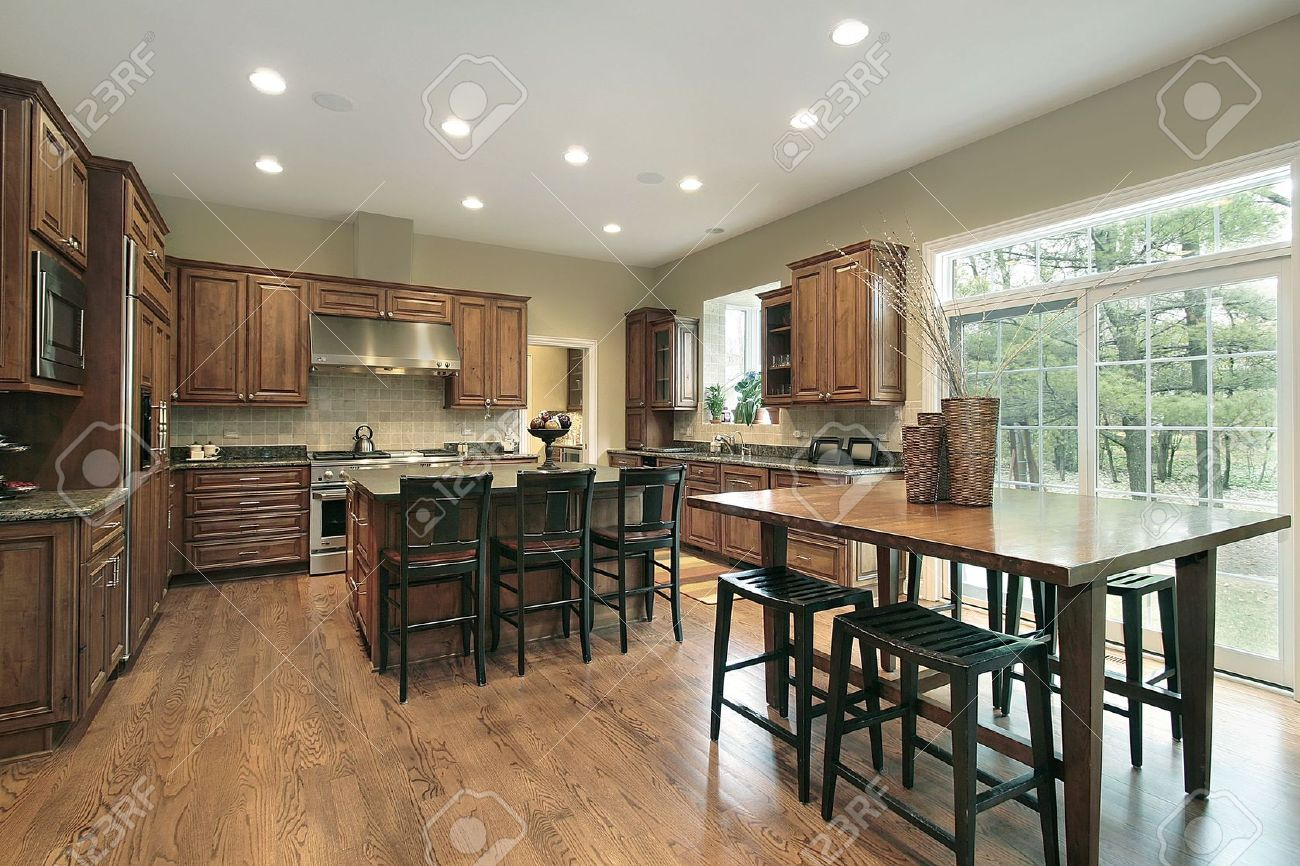 luxury kitchen with wood cabinets and eating area stock photo
