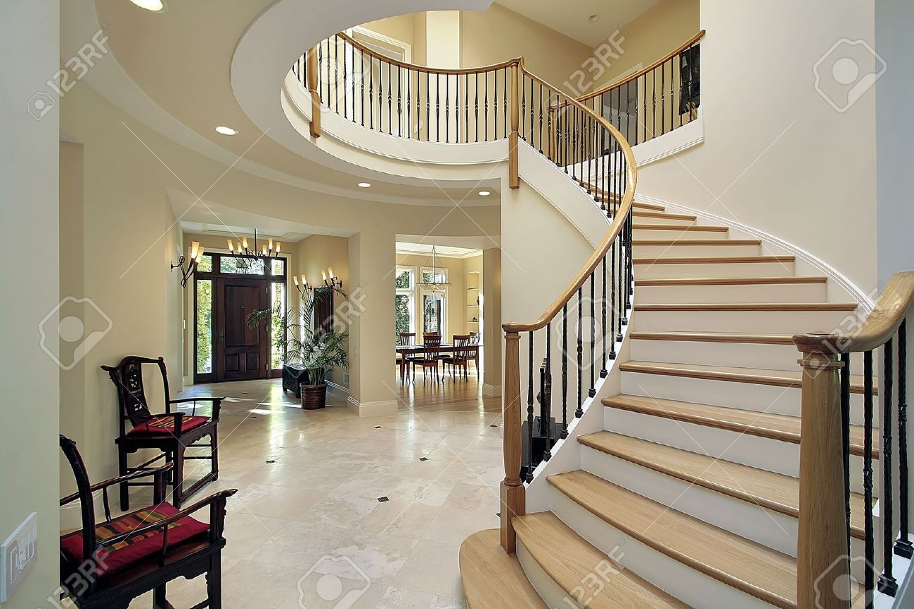 Foyer in luxury home with curved staircase stock photo, picture ...