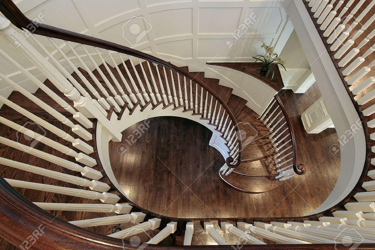 escalera de caracol en casa con barandilla de madera de lujo foto de archivo