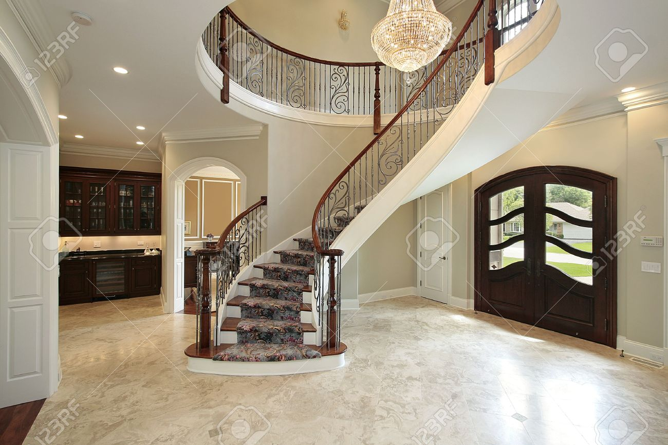 Foyer in new construction home with curved staircase stock photo ...