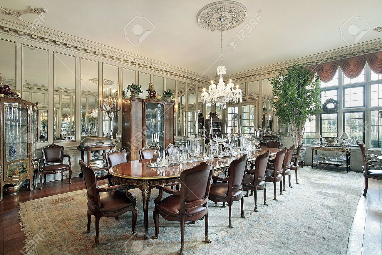 Traditional Home Dining Rooms formal dining room in traditional home with wall mirrors stock