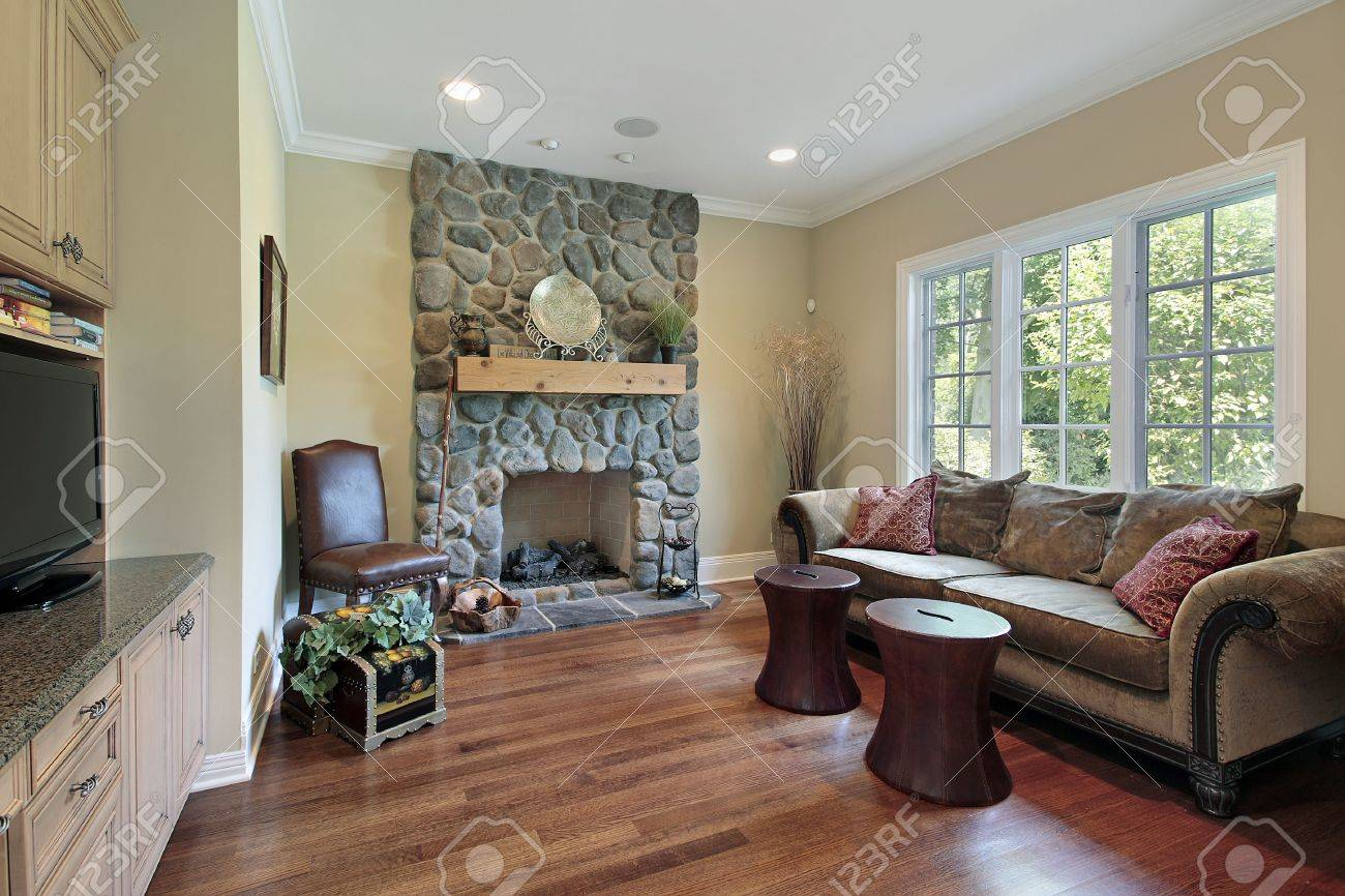 family room in luxury home with stone fireplace stock photo