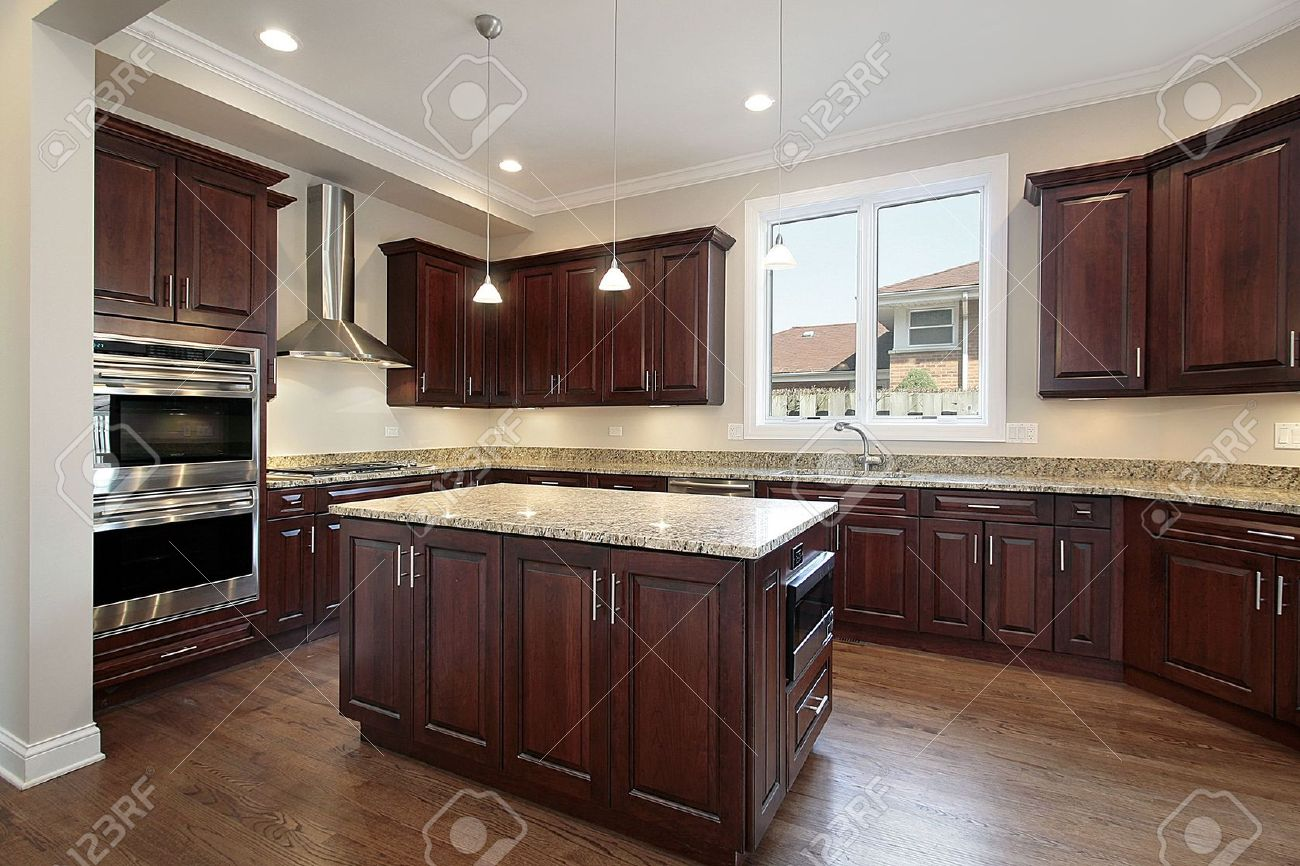 6738658 Kitchen in new construction home with cherry wood cabinetry Stock Photo