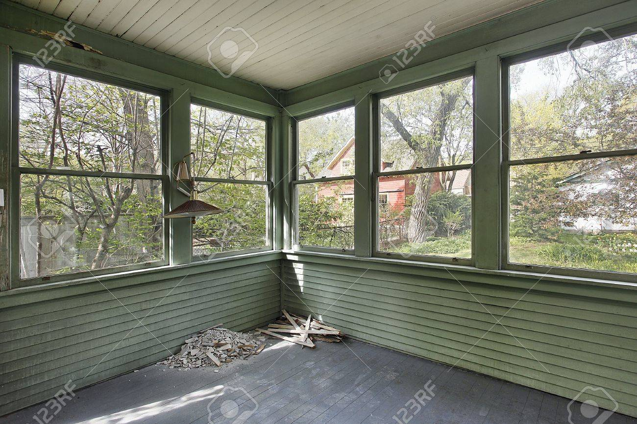 Green porch with wall of windows in old abandoned home Stock Photo - 7180351