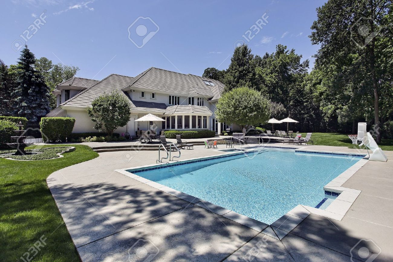 swimming pool and deck in back of luxury home stock photo picture