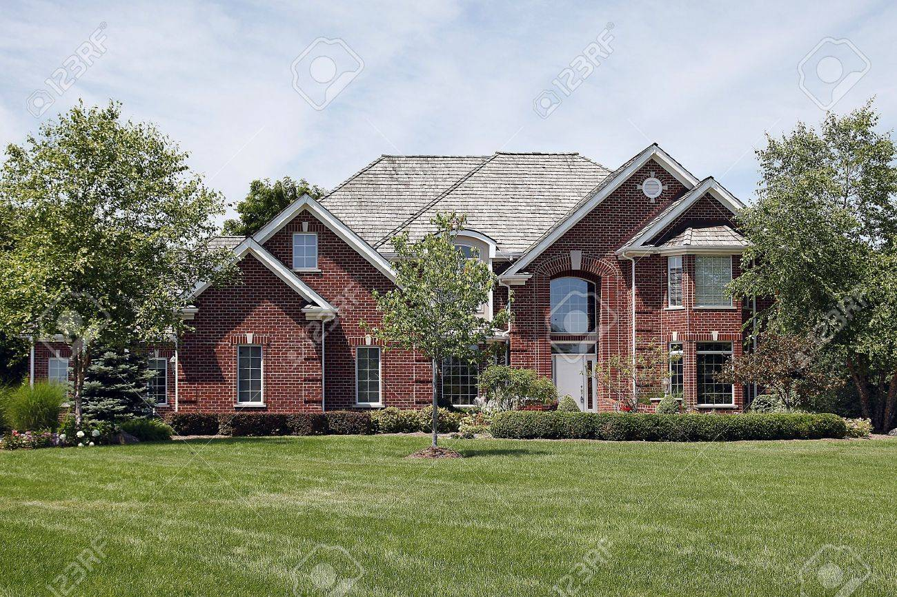 Large Brick Home With Large Window Above Front Door Stock Photo