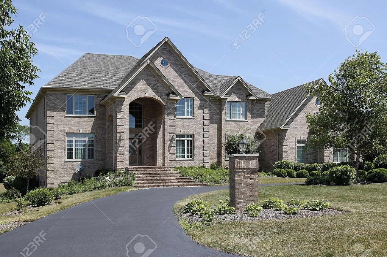 Large brick home with steps up to arched entry Stock Photo - 10293117