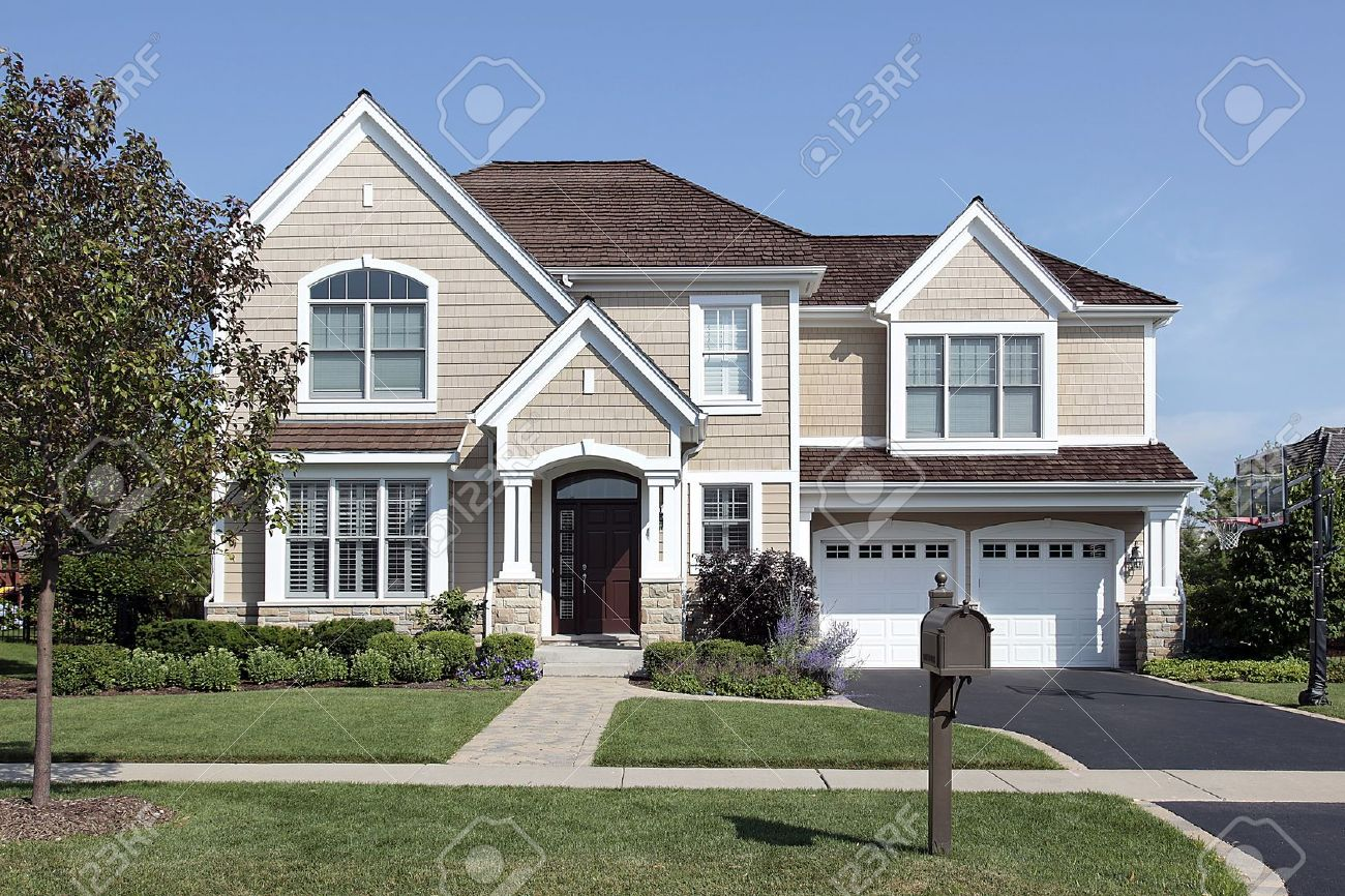 Home in suburbs with arched entry and brown cedar roof Stock Photo - 10293065