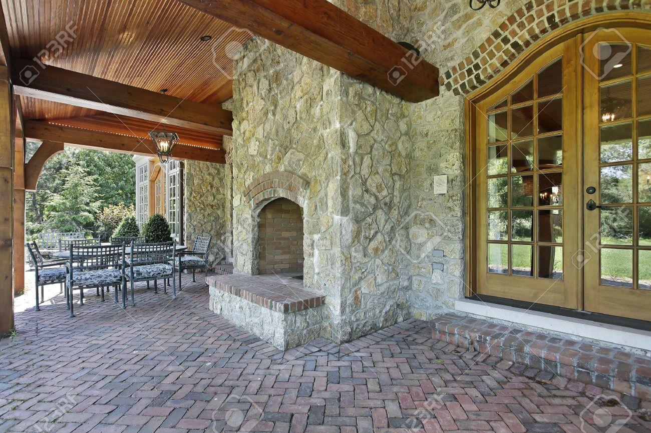 patio de ladrillo fuera de casa con chimenea de piedra de lujo foto de archivo