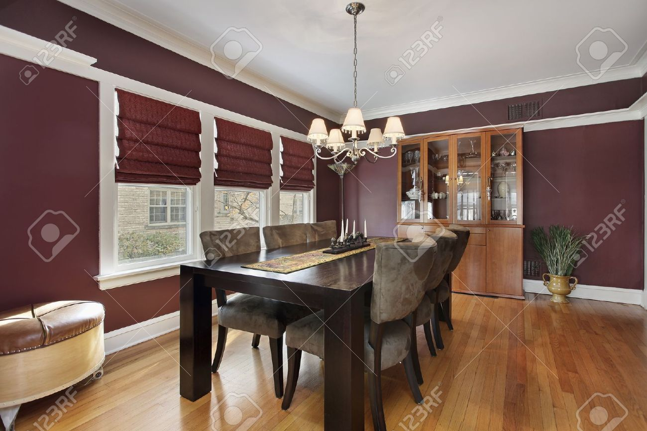 dining room with maroon walls and three windows stock photo