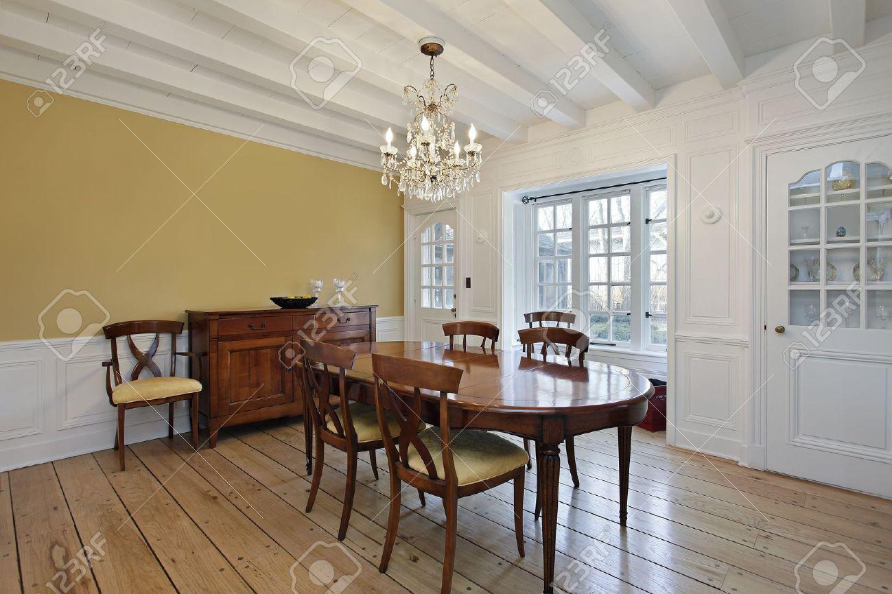 wohn-esszimmer mit weißem holz deckenbalken und gold wände
