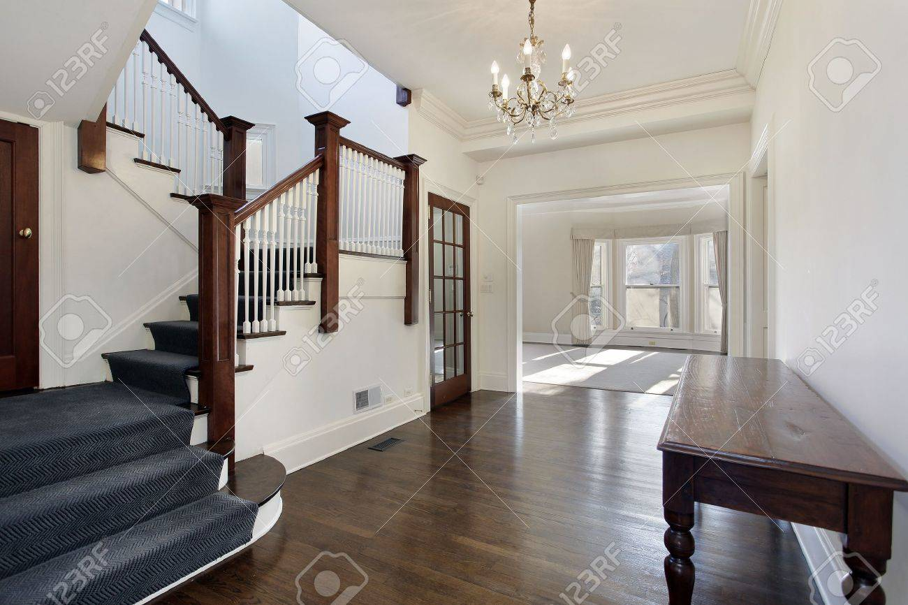 Foyer in traditional home with brown and white staircase stock ...