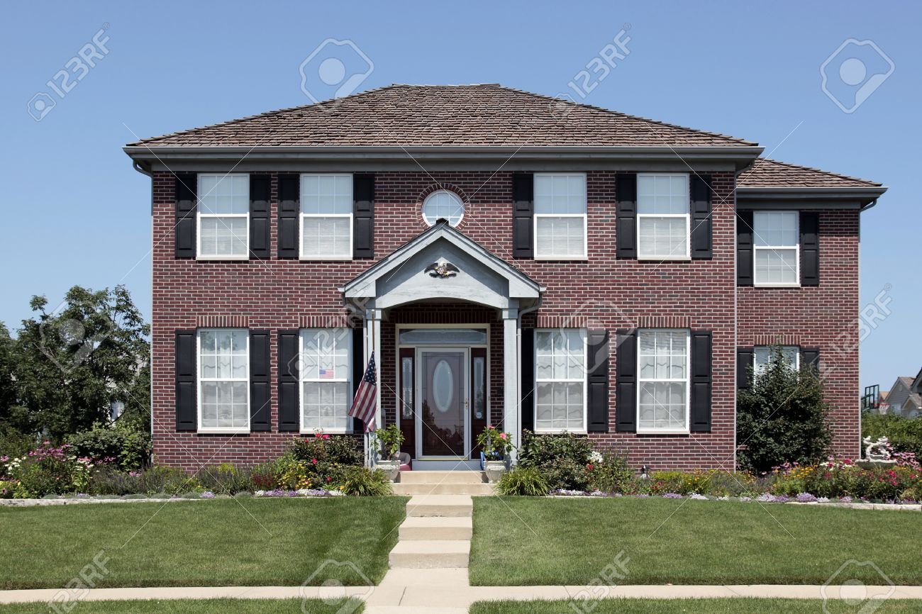 Brick home with arched entry and American flag Stock Photo - 10537576