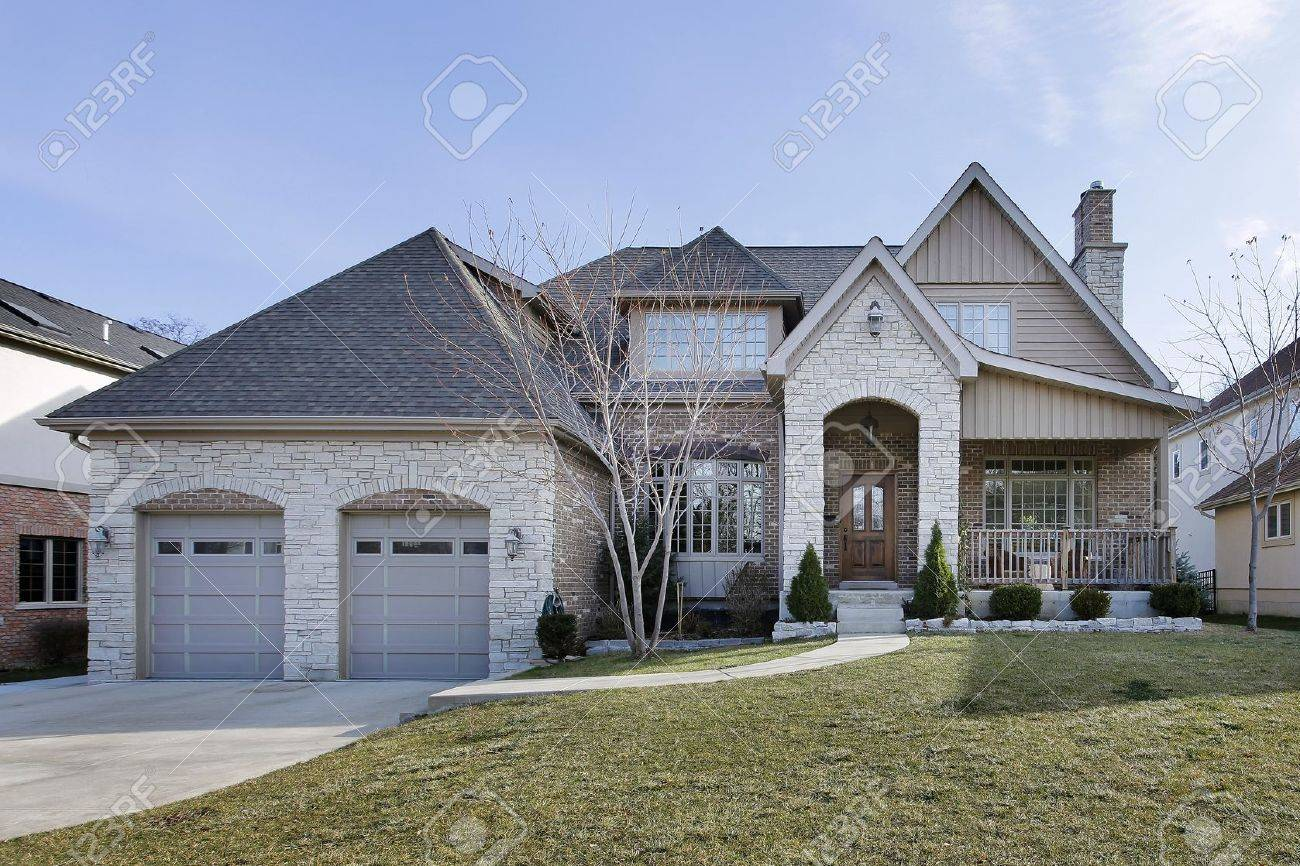 stone and brick home in winter with arched entry stock photo 10537595