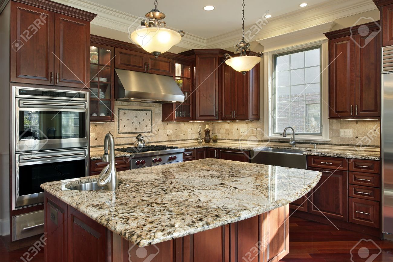 Kitchen With Granite Island And Cherry Wood Cabinetry Stock Photo ...