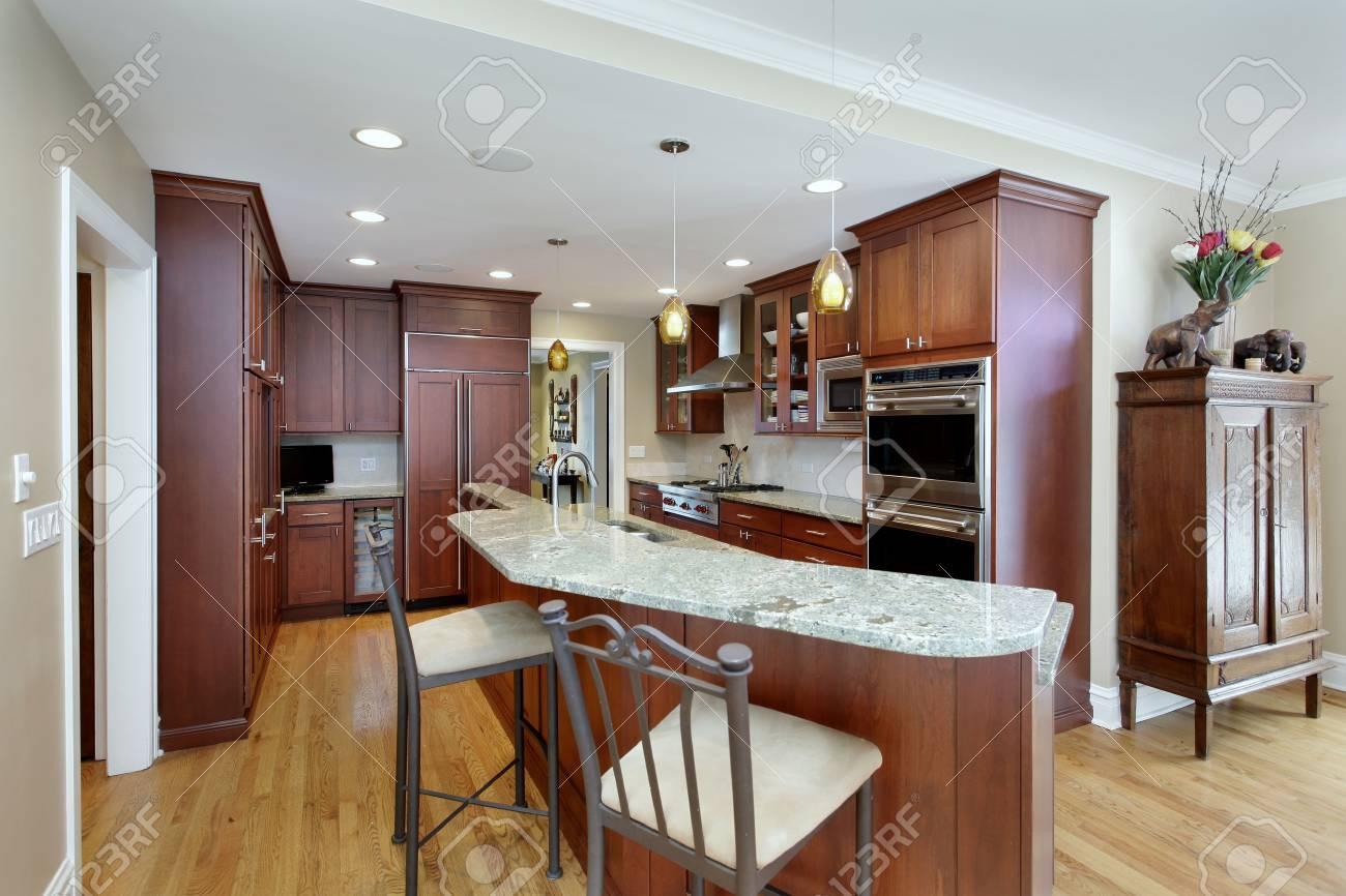 Cuisine moderne avec étagère à deux étages et armoires en cerisier.