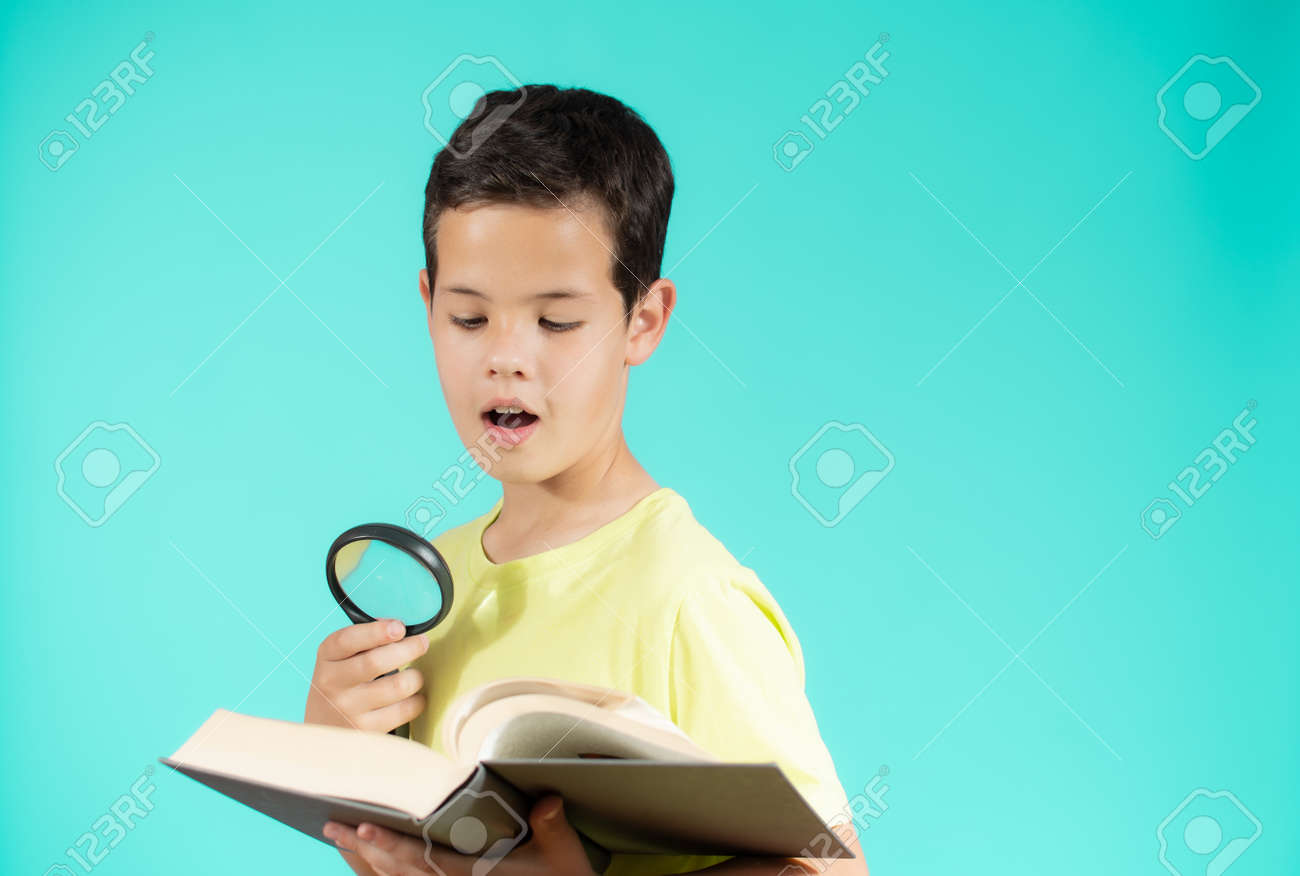 Young boy looking through a magnifying glass while reading an open book, isolated on green background - 166115483