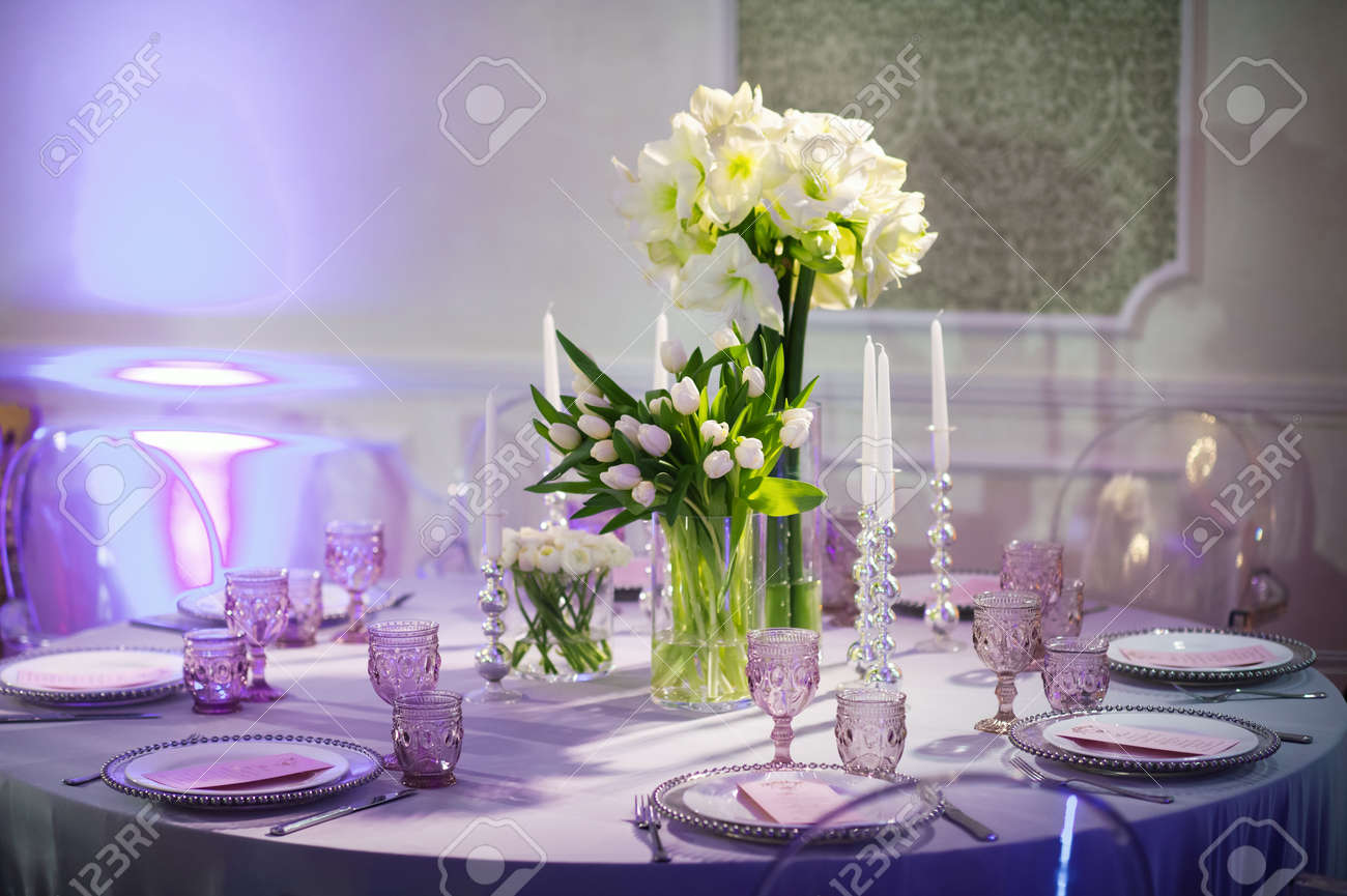 decoration of a festive dinner with flowers of lilies and tulips on the wedding table in the interior of the restaurant. Decorated table for a celebration in purple tones. - 157069491