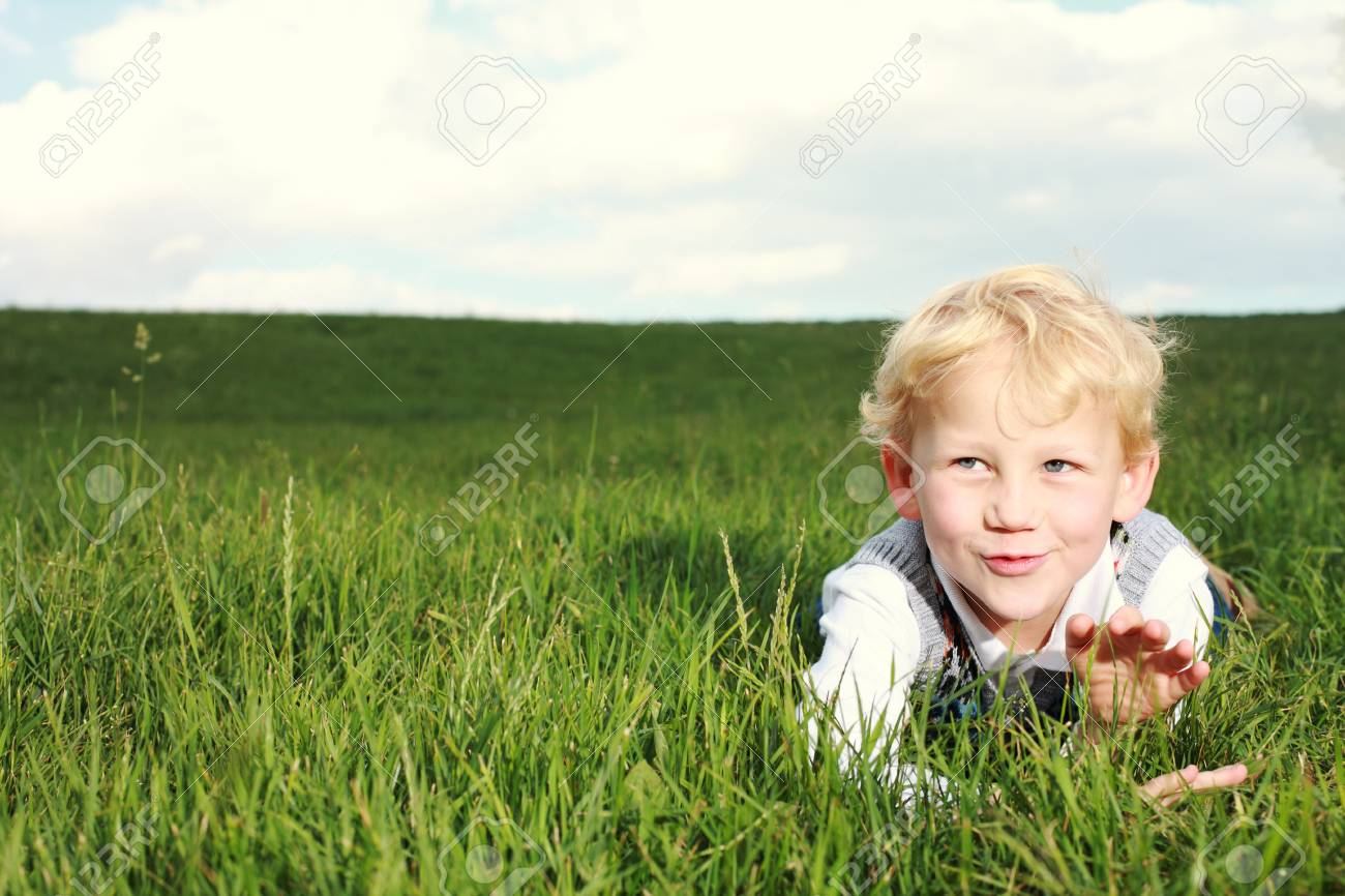 Happy little boy lying in an open green grassy field clapping his hands and showing appreciation with a mischievous smile Stock Photo - 14321735