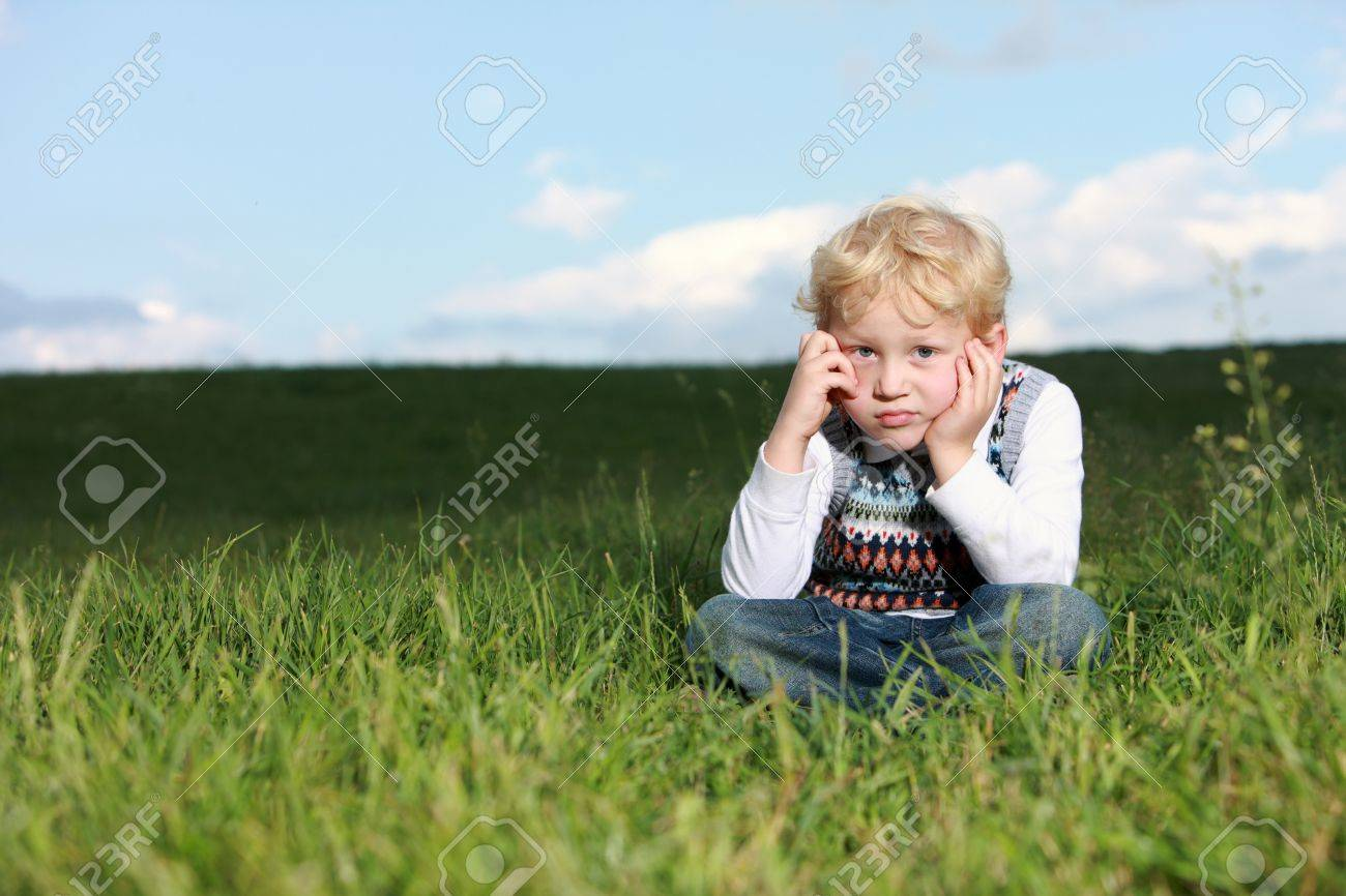 Glum little boy sitting in grass with his chin resting on his hands and a despondent expression Stock Photo - 14321737