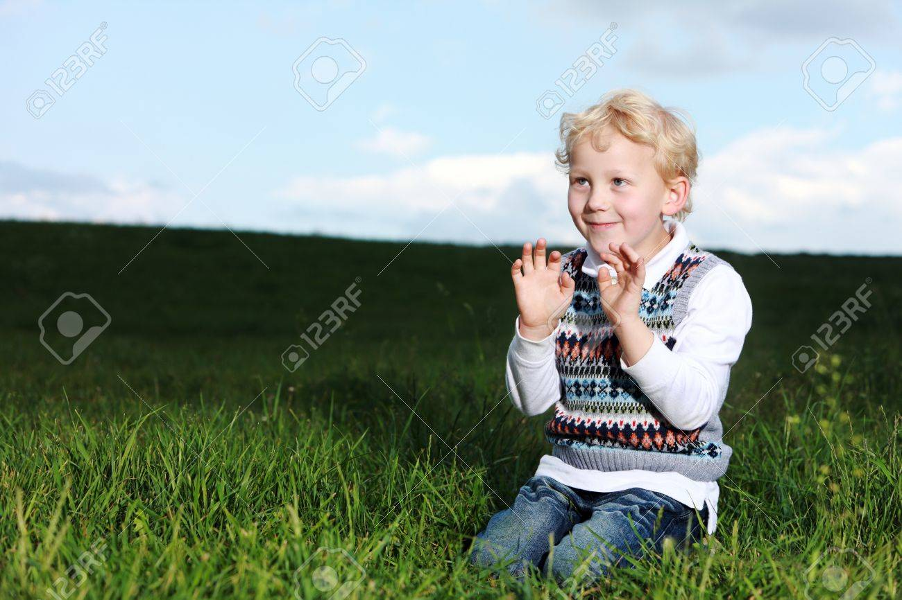 Impish little boy kneeling in a shaft of sunshine in green field smiling as he raises his hands to his chest Stock Photo - 14321729