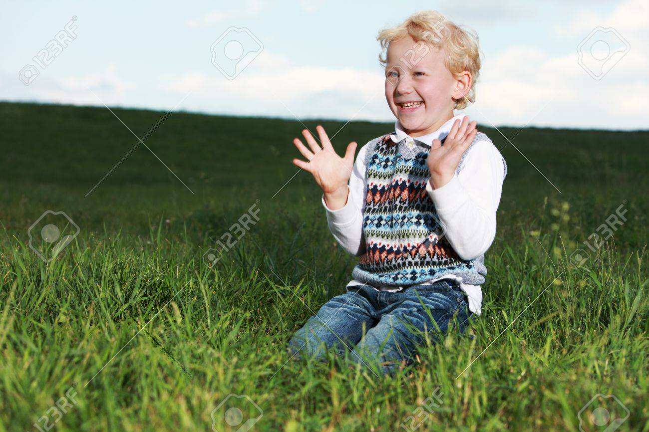 Little boy kneeling in a large grassy green field clapping his hands in glee Stock Photo - 14321733