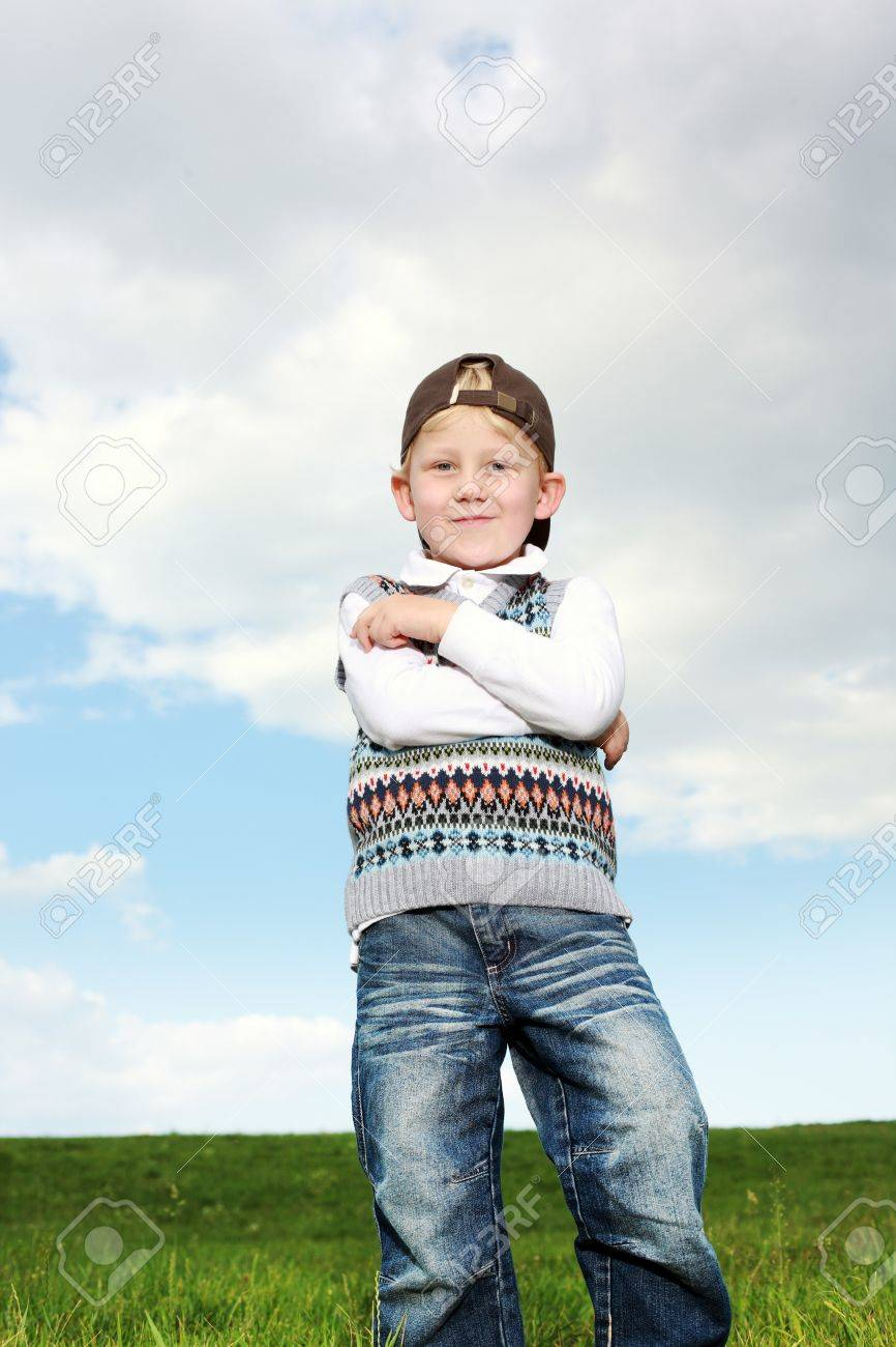 Smiling confident young boy standing with his arms folded over his chest and looking down at the camera with amusement Stock Photo - 14321731