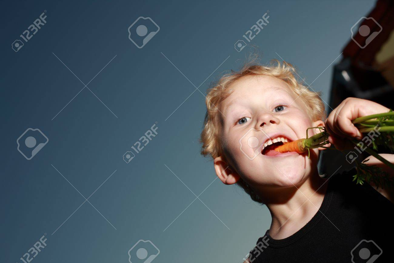 Low angle view of a young blonde boy munching a freshly pulled carrot which still has its leaves Stock Photo - 14321739
