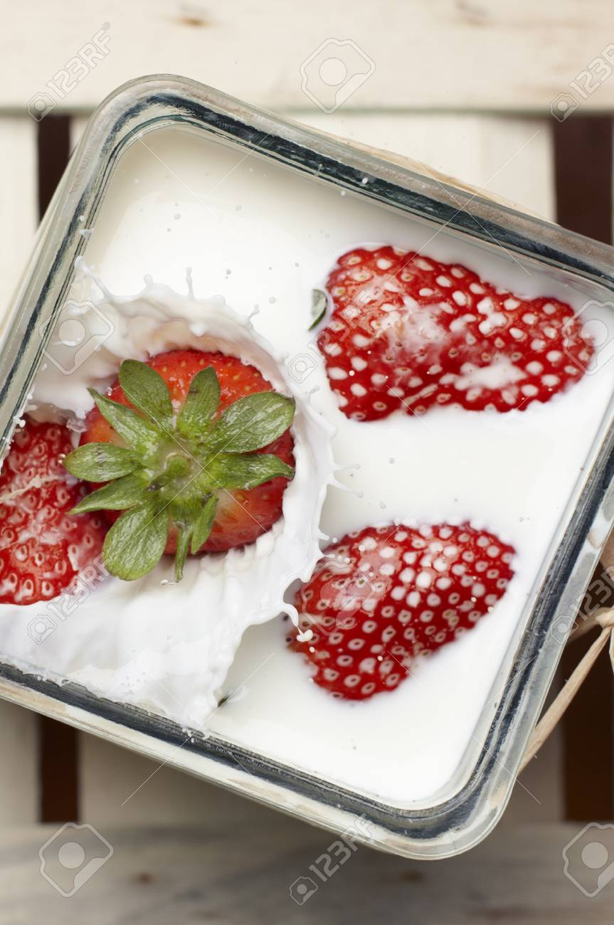 Large ripe red strawberry falling and splashing into milk containing three other floating strawberries Stock Photo - 14273334