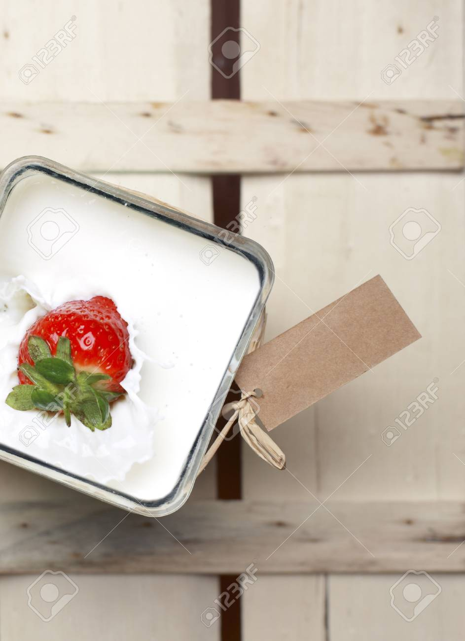 Overhead view of a luscious ripe red whole strawberry splashing into a container of milk Stock Photo - 14273332