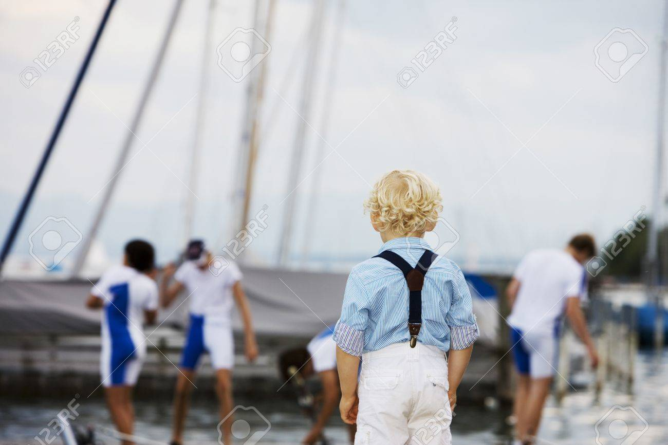 Little boy with curly blonde hair standing with his back to the camera watching his favourite sports team Stock Photo - 14313948