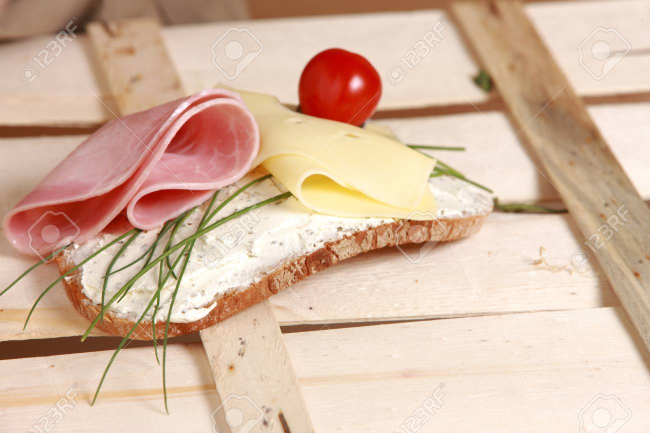 Open sandwich on a slice of rye bread with ham and cheese garnished with fresh chives and a cocktail tomato Stock Photo - 14273343