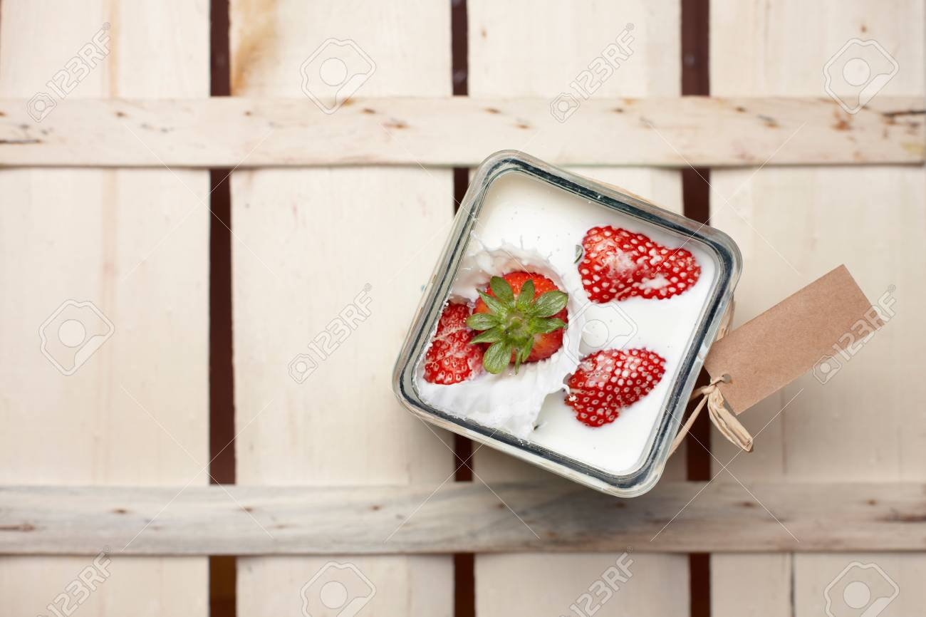 Overhead view of a ripe red strawberry being dropped into a container of milk with a splash Stock Photo - 14273345