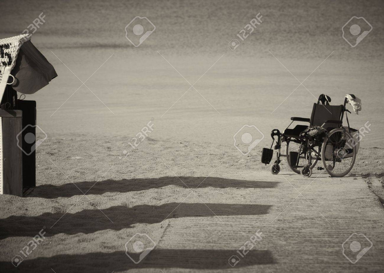 Monochrome image of an abandoned empty wheelchair parked on the edge of sand as it was not able to be wheeled any further over the soft terrain Stock Photo - 14530000