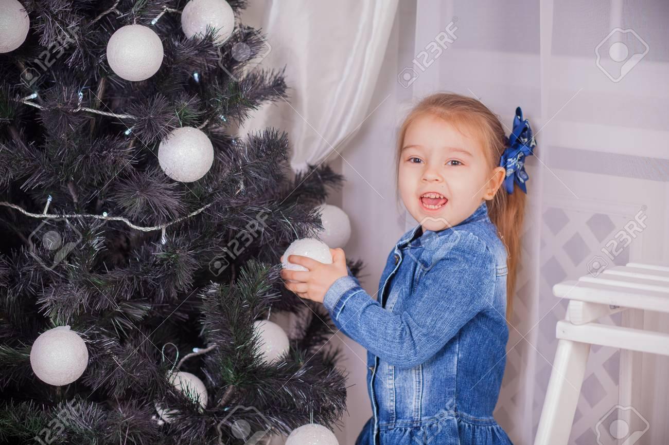 Kleines Mädchen mit Weihnachtsgeschenke in der Nähe eines Weihnachtsbaumes zu Hause