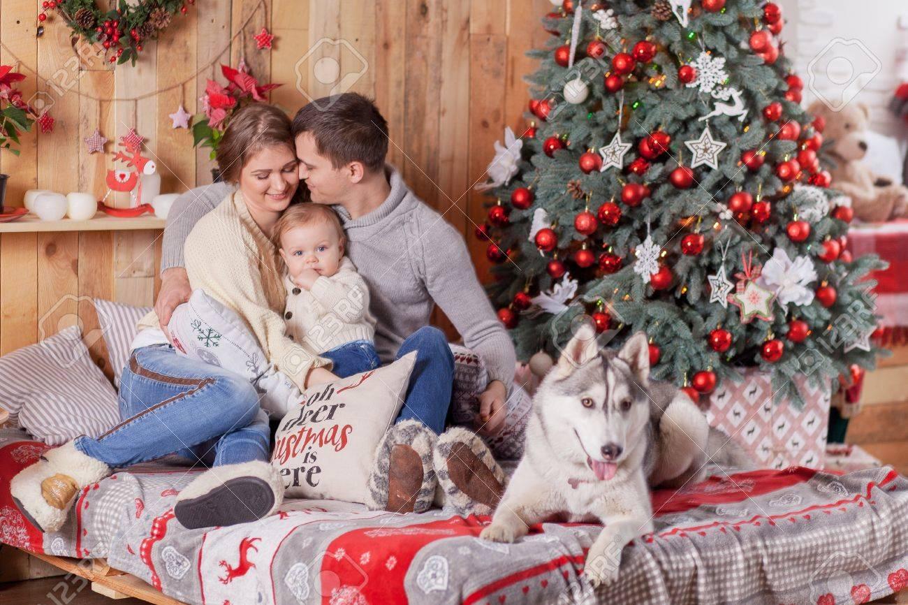 Happy family and a dog Siberian Husky near the fireplace around..
