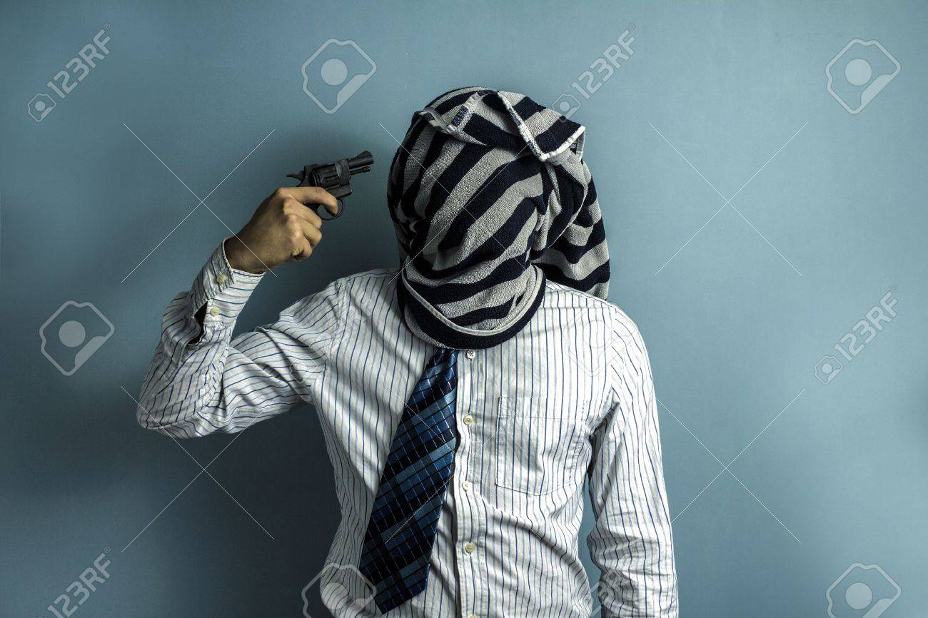 A man with a towel areound his head pointing a gun at himself Stock Photo - 17805575
