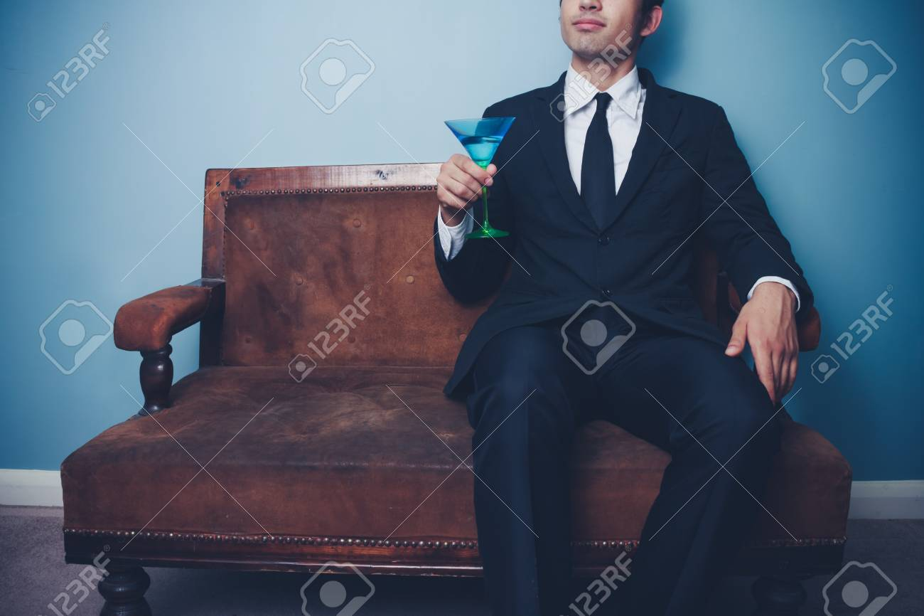 Young businessman on old vintage sofa celebrating with a cocktail Stock Photo - 22141148