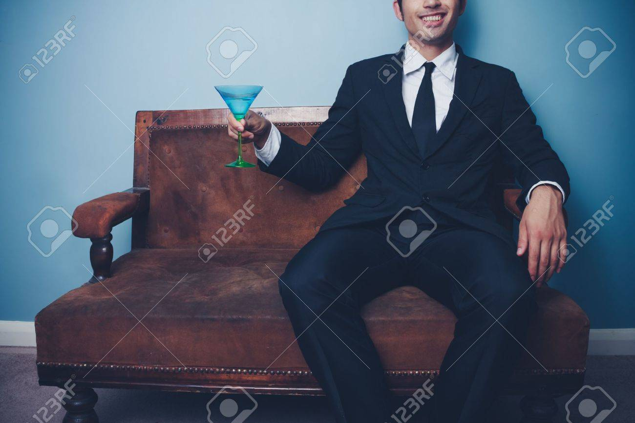 Young businessman on old vintage sofa toasting with a cocktail Stock Photo - 22159494