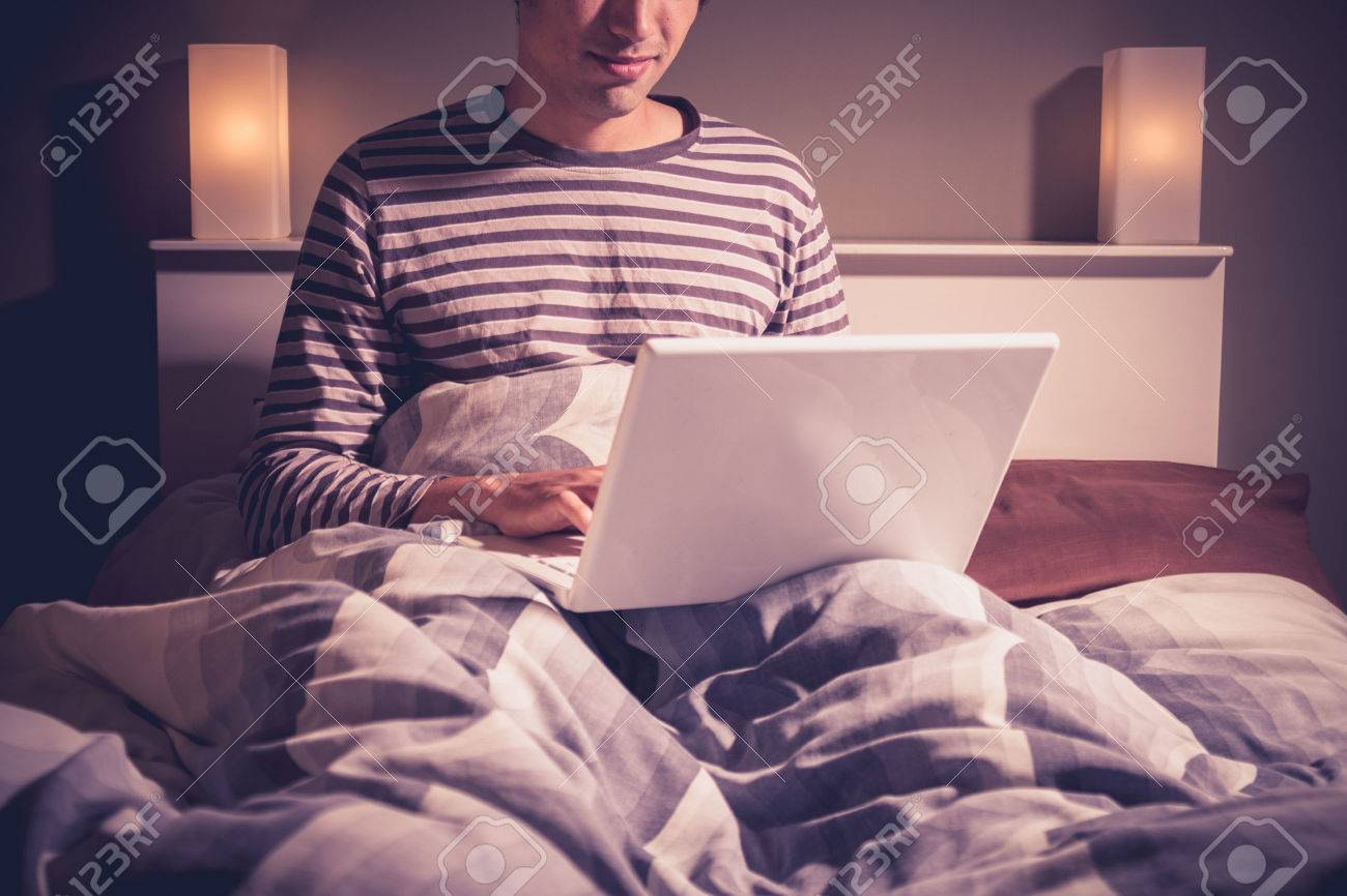 Young man in bed using laptop computer Stock Photo - 22478574
