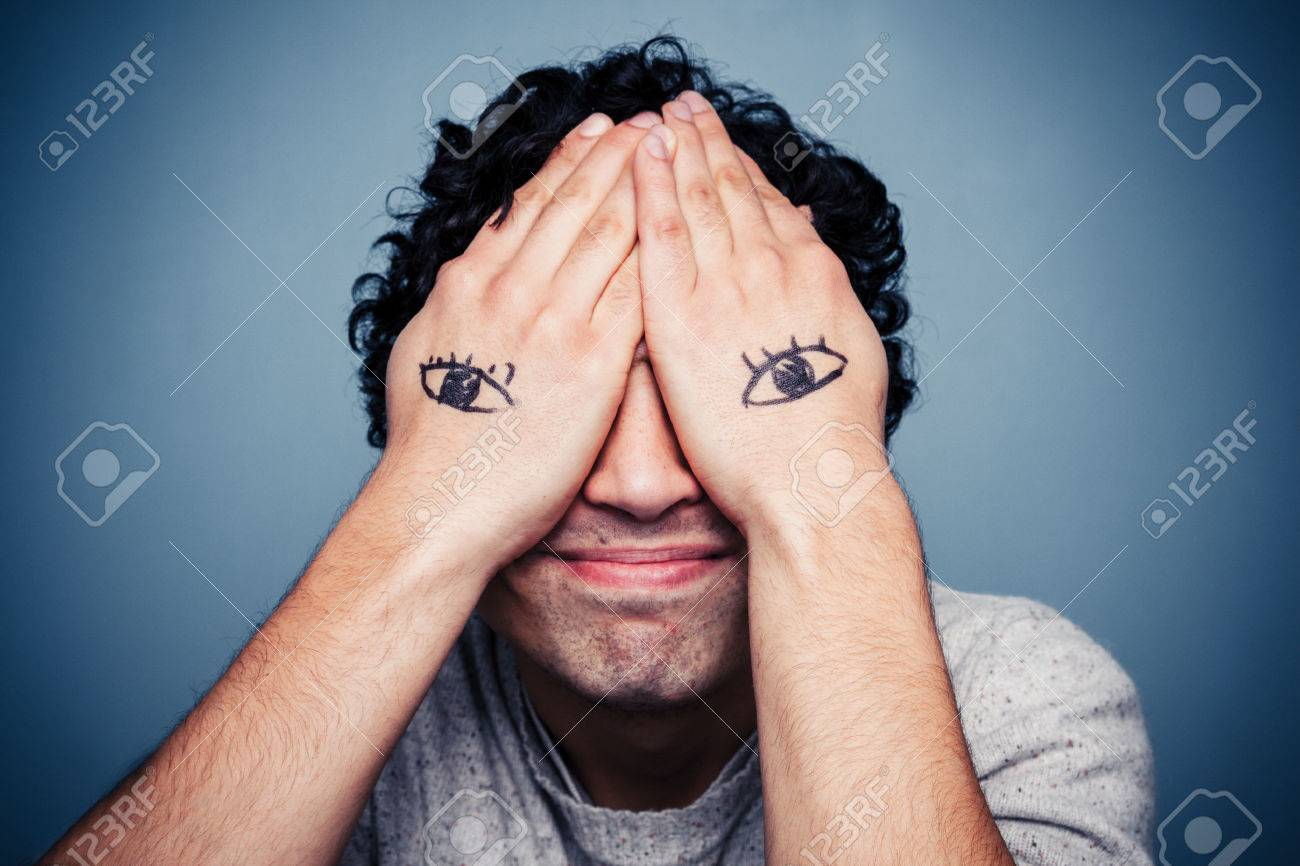 [24428122-Man-with-eyes-painted-on-his-hands-covering-his-face-Stock-Photo]