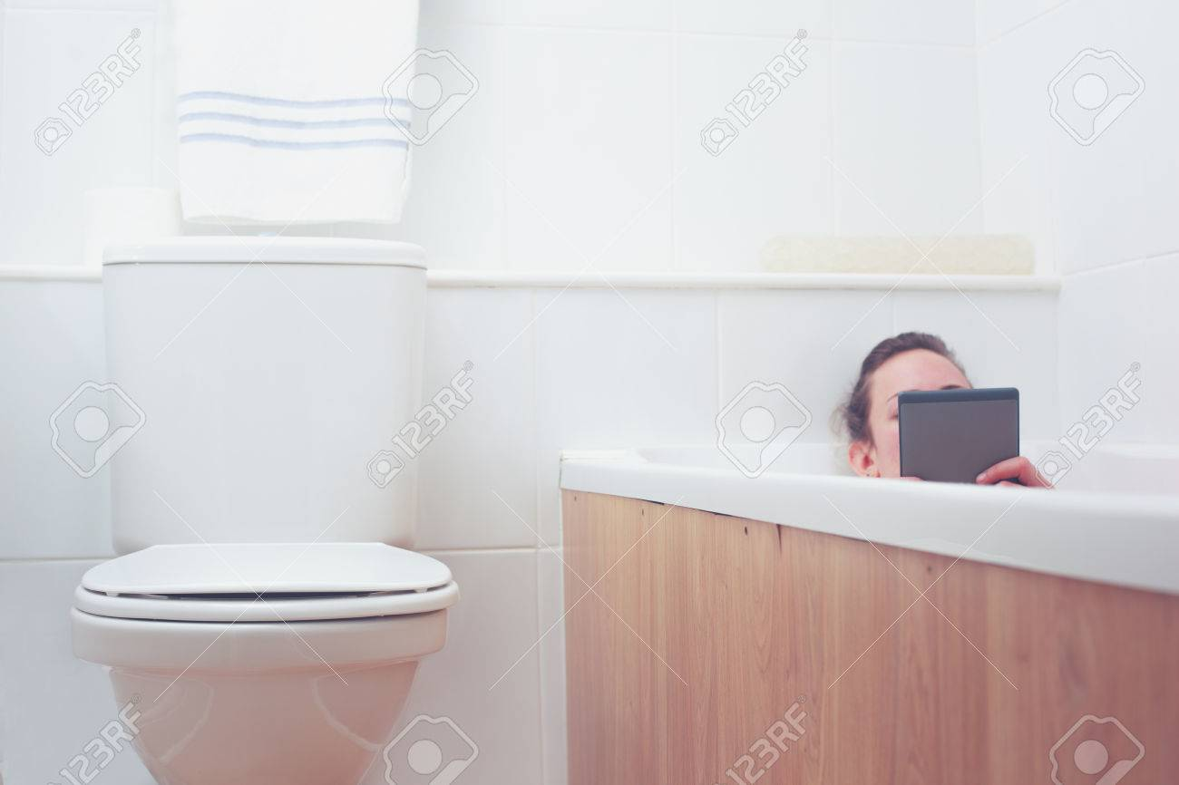 Young Woman In A Bathtub Is Reading On A Tablet Stock Photo, Picture ...