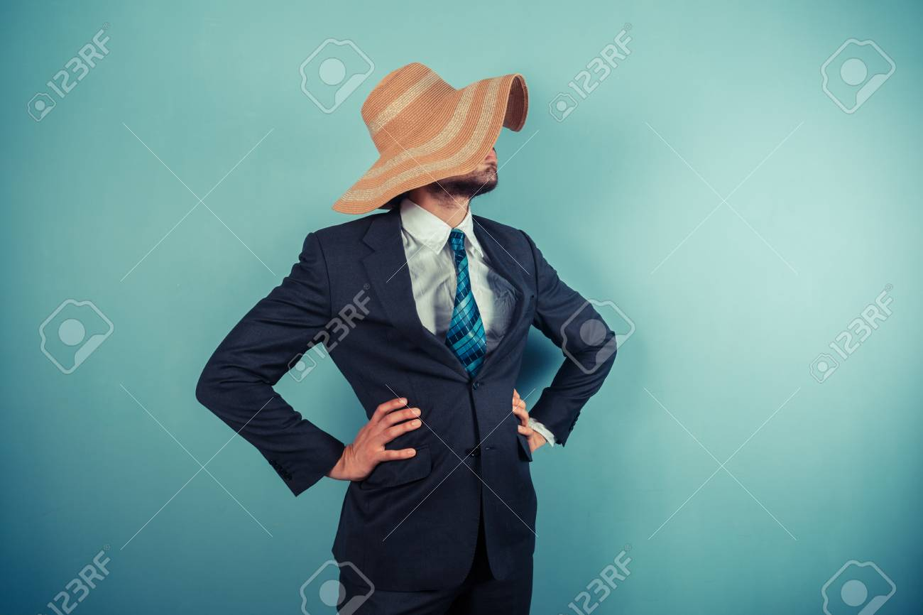 A young businessman is wearing a large beach hat Stock Photo - 29625548